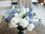 a beautiful wedding centerpiece of a black urn, white and blue blooms and some candles is a lovely arrangement