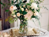 a romantic summer wedding centerpiece of a clear vase with blush blooms and lots of leaves for more texture