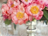 a bright vintage-inspired summer wedding centerpiece of a silver vase and coral blooms with leaves is a lovely and bright idea
