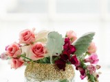 a clear vase with gold glitter and pink blooms and leaves looks chic, glam and bright and will accent your summer tablescape