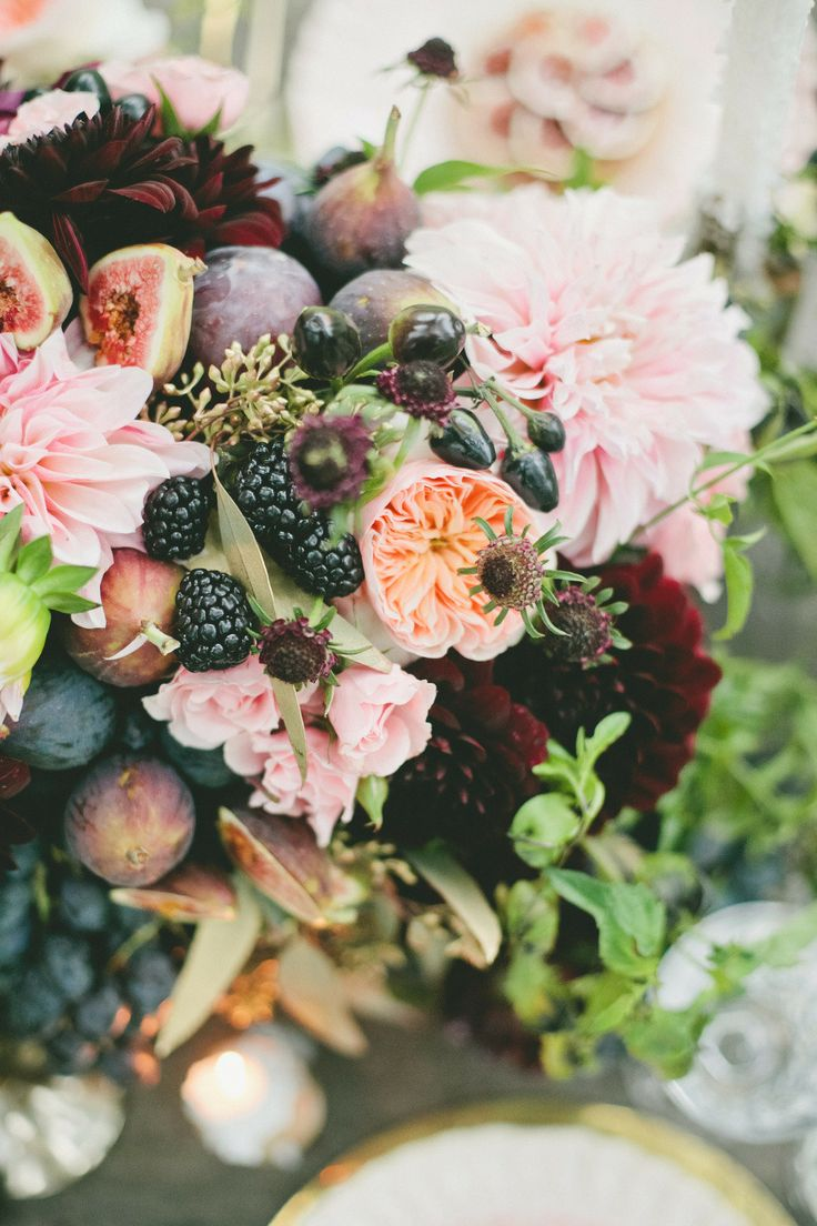 a lush wedding centerpiece of blush and peachy blooms, berries, fruit and some greenery looks very lush and bright
