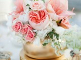 a romantic summer wedding centerpiece of a gold vase, pink blooms, white flowers and leaves looks chic, glam and fresh