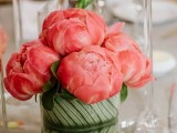 a vivacious summer wedding centerpiece of coral peonies and a vase wrapped with a large leaf is a stylish and inspiring summer wedding centerpiece
