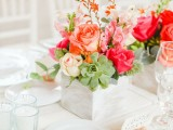 a vivacious summer wedding centerpiece of a wooden box and bright blooms – coral, blush, fuchsia ones and succulents and blooming branches