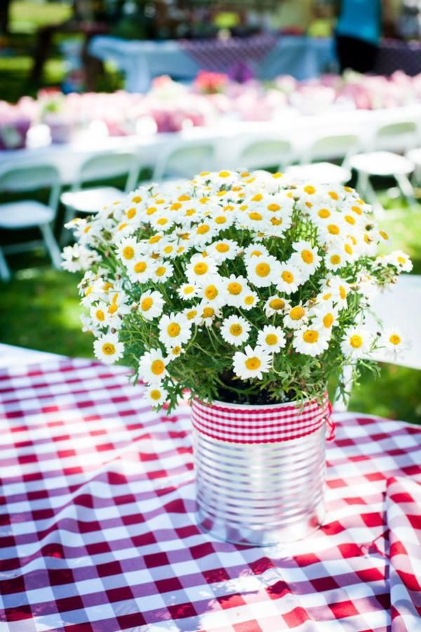 a rustic summer wedding centerpiece of a metal bucket, with daisies and a plaid wrap is a simple and very cute decoration