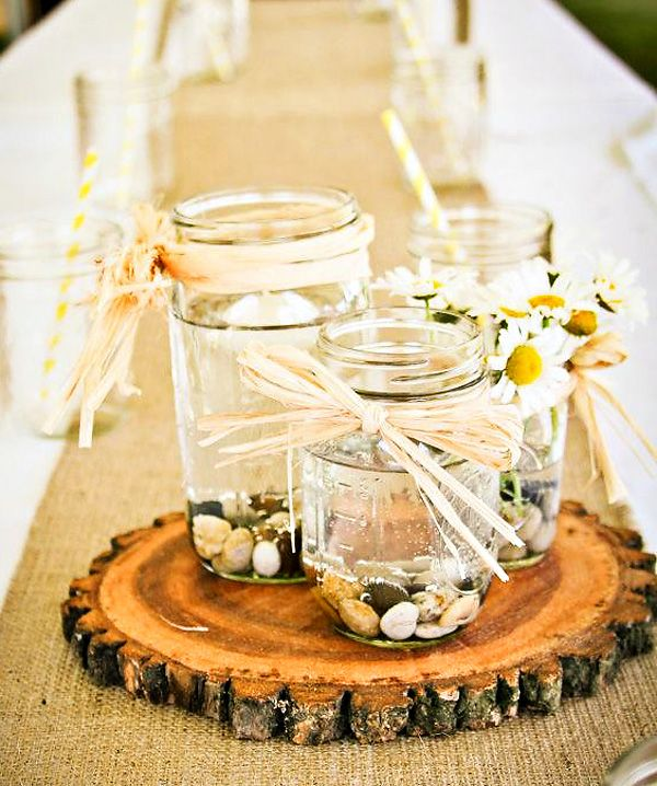 a simple summer wedding centerpiece of a wood slice, jars with pebbles, floating candles and daisies for a relaxed woodland summer wedding