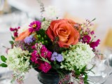 a bright refined wedding centerpiece of a vintage urn, bright orange, fuchsia, purple, green and blue blooms looks lovely