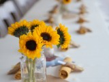 a simple rustic summer wedding centerpiece of a clear jar and sunflowers will add color and a natural feel to the space