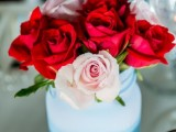 a colorful summer wedding centerpiece of an ombre blue jar and red and blush roses is easy to compose yourself