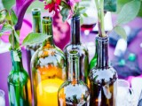 a bold summer wedding centerpiece of wine bottles, bright blooms and greenery and a candle lantern will fit a vineyard summer wedding