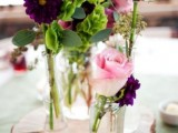 a bright relaxed summer wedding centerpiece of a wood slice, vases and jars, pink and purple blooms and greenery