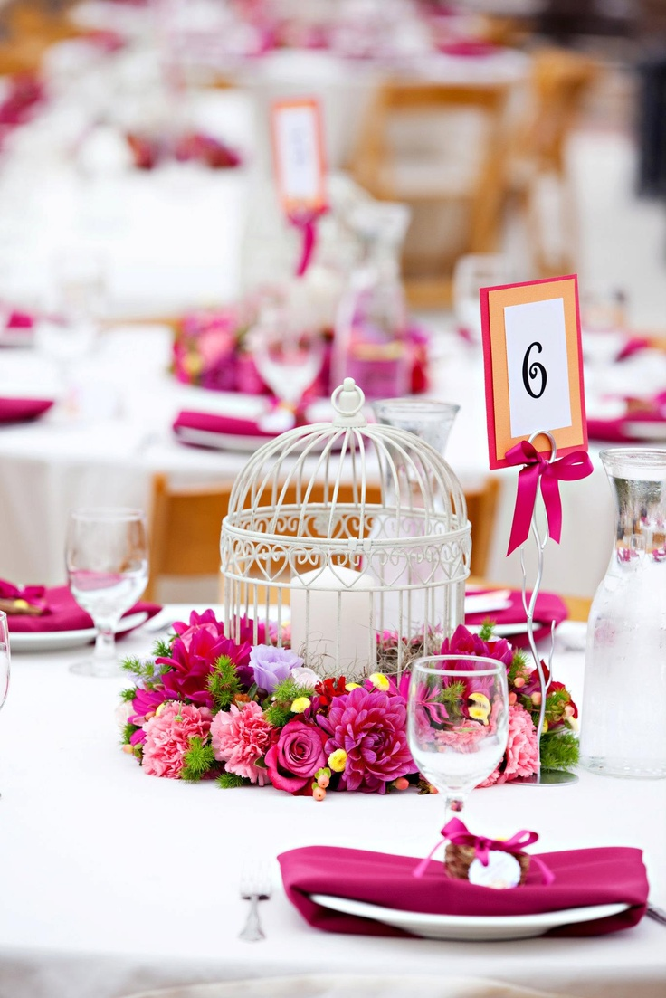 a refined summer wedding centerpiece of a candle in a cage, bright pink and fuchsia blooms and leaves