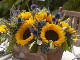 a colorful summer wedding centerpiece of a wooden box, sunflowers, thistles, allium and lavender features much color and texture
