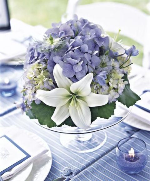 a romantic pastel summer wedding centerpiece of a clear stand with blue and white blooms and foliage is delicate and chic