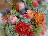 a colorful summer wedding centerpiece of a wooden box, green, orange, pink, red blooms, thistles and greenery is a lovely and beautiful idea