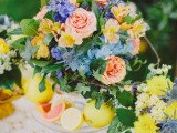 a vivid summer wedding centerpiece of yellow, blush, blue blooms, thistles and leaves and citrus is summer-inspiring