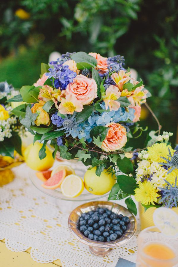 a vivid summer wedding centerpiece of yellow, blush, blue blooms, thistles and leaves and citrus is summer inspiring
