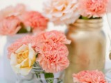 a vivacious summer wedding centerpiece of gold, white and clear vases and jars, blush, peachy and coral blooms is chic and stylish