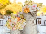 a pastel summer wedding centerpiece of tree stumps, peachy, blush, white and yellow blooms, candles in tall glasses