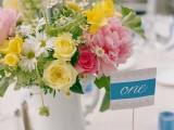a vibrant summer wedding centerpiece of a white jug, yellow, pink and white blooms and greenery and a card on a stand