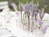 a chic and simple summer wedding centerpiece of a wire basket, clear vases with lavender and some lavender around is refined