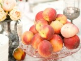 a lovely summer wedding centerpiece of a silver teapot with peachy blooms, a glass stand with fresh peaches is amazing and summery-like