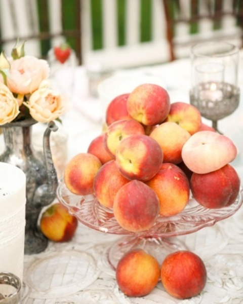 a lovely summer wedding centerpiece of a silver teapot with peachy blooms, a glass stand with fresh peaches is amazing and summery like
