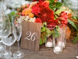a bold summer wedding centerpiece of red, orange and peachy blooms, leaves, candles and a wooden table number