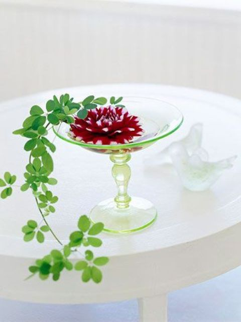 a green glass stand with a burgundy bloom and cascading greenery is a refined and chic summer wedding centerpiece