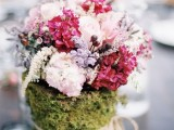 a summer woodland wedding centerpiece of light pink, blush and fuchsia blooms and a vase wrapped in moss