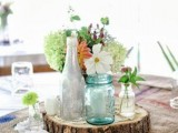a rustic summer wedding centerpiece of a wood slice, neutral and green blooms and bottles and jars