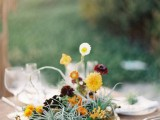 a whimsy wedding centerpiece of a gold bowl, yellow, orange and deep purple blooms and air plants will make your tablescape cooler