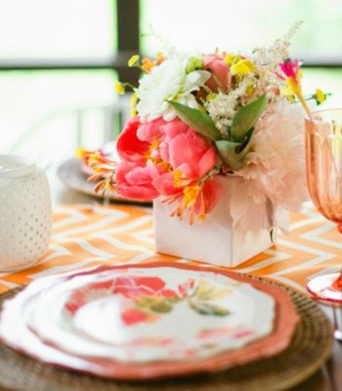 a vivacious summer wedding centerpiece of a white box and blush, white, coral and yellow blooms and textural greenery