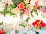 a colorful refined summer wedding centerpiece of a silver stand, white, blush, pink blooms, succulents and cascading greenery is very vibrant