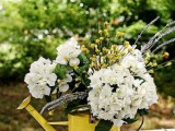 a rustic summer wedding centerpiece of a yellow watering can, white and yellow blooms and some lavender