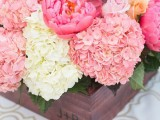 a dark stained box with pink, coral pink and white blooms and leaves is a vivid summer wedding centerpiece