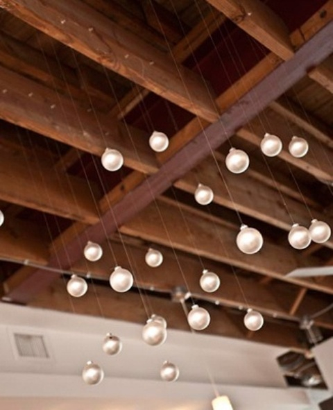 white ornaments hanging over the reception will give a snowy and holiday feel to the wedding decor