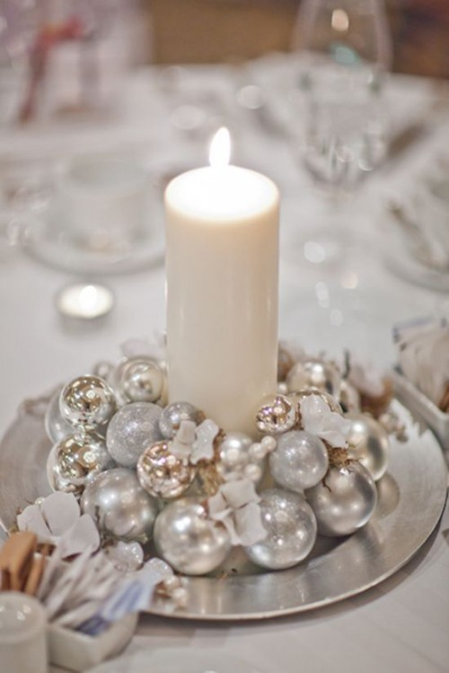 a pretty winter wedding centerpiece of a bowl with shiny Christmas ornaments and a single pillar candle in the middle