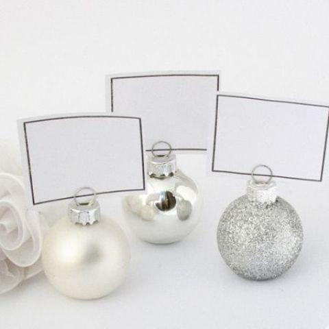 silver, glitter and mother of pearl ornaments to hold cards at the wedding tables