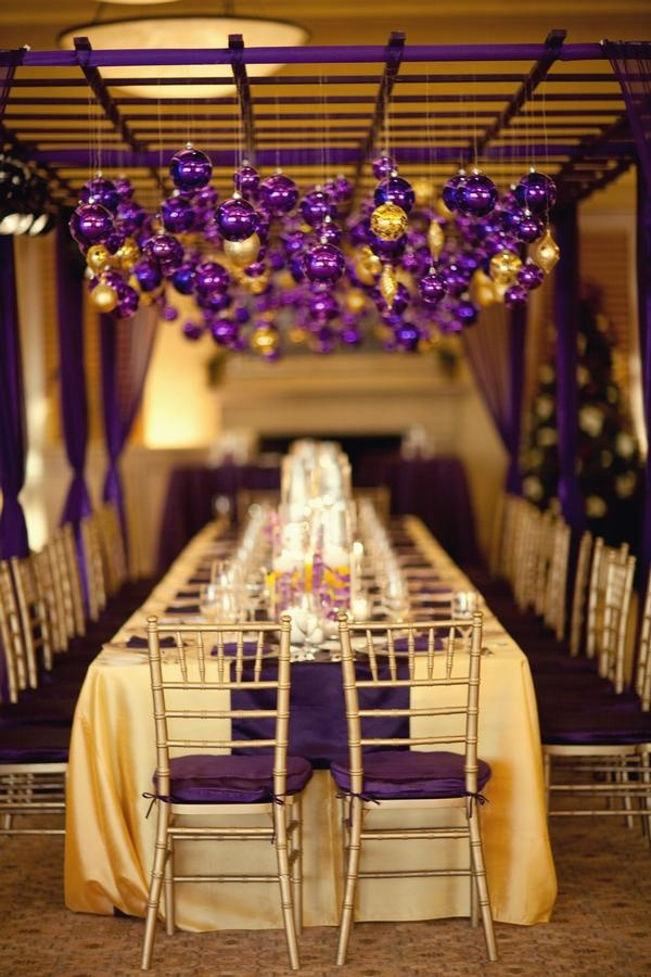 a purple and gold wedding reception with ornaments overhead looks bold, bright and colorful and very festive like