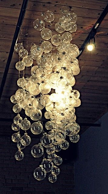 a chandelier made of white Christmas ornaments is a creative and fun idea with a strong holiday spirit
