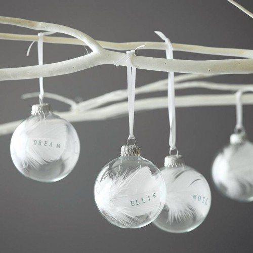 sheer ornaments filled with white feathers and with marks hanging on your Christmas tree will give the wedding a holiday feel