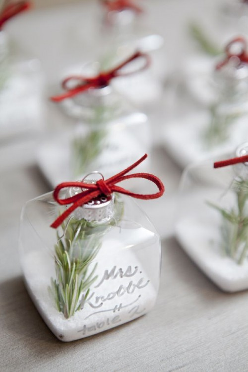 sheer square ornaments filled with faux snow, evergreens and with red bows are nice escort cards and favors