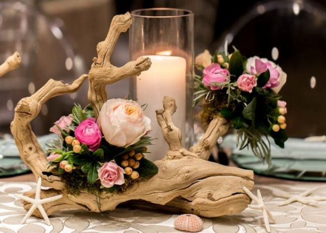 a driftwood wedding centerpiece of blush and pink blooms,greenery, a large candle and starfish