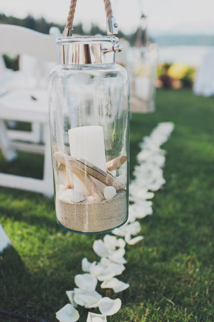 a jar with sand, pebbles, shells and a candle is great to line up the wedding aisle and make it cool
