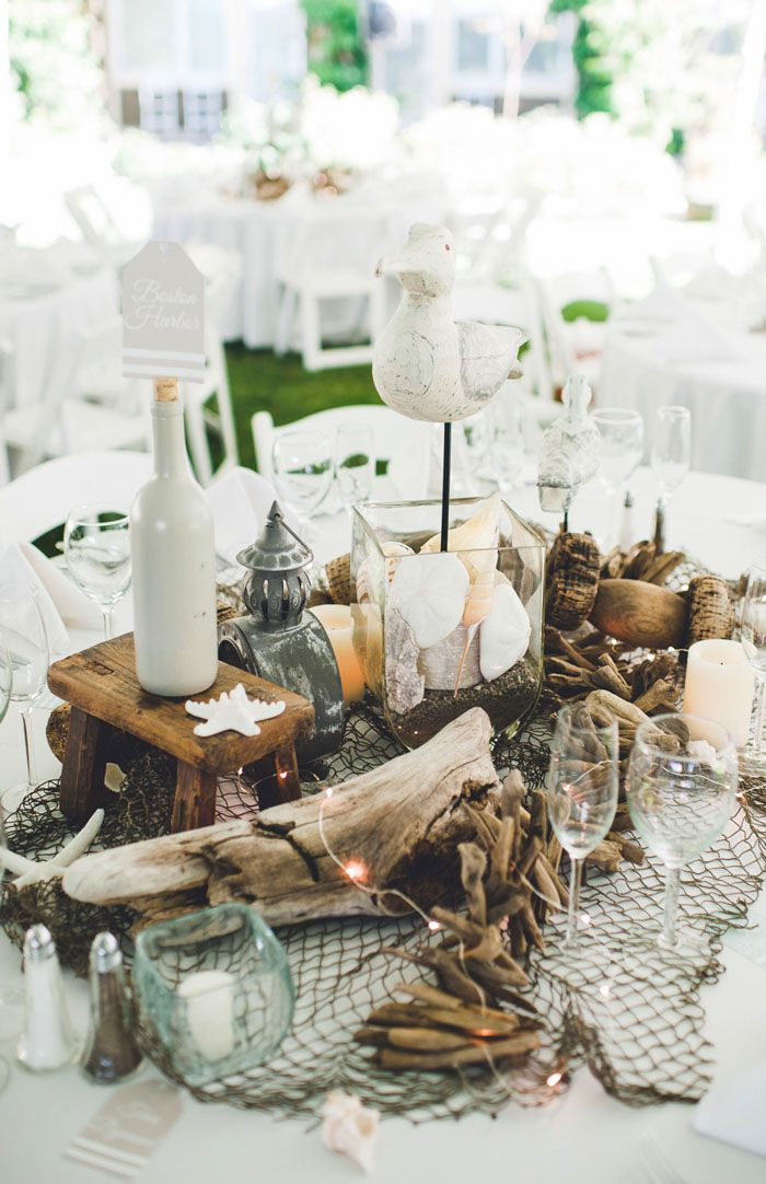 a cool beach wedding decoration of driftwood, candles, seashells, starfish, pebbles, fishnet and bottles