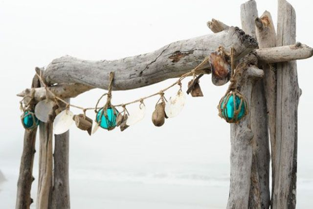 a driftwood wedding arch with seashells, driftwood and buoys is great to install it right on the beach