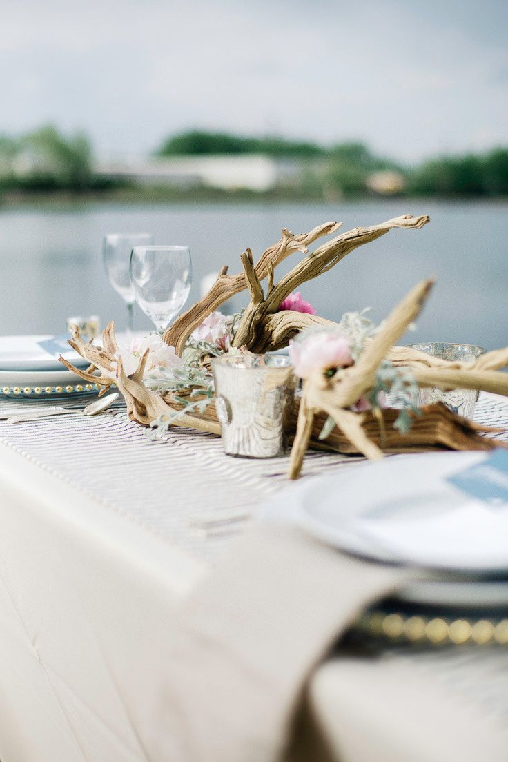 a dirftwood wedding centerpiece of greenery and pink blooms plus some candles is a stylish idea