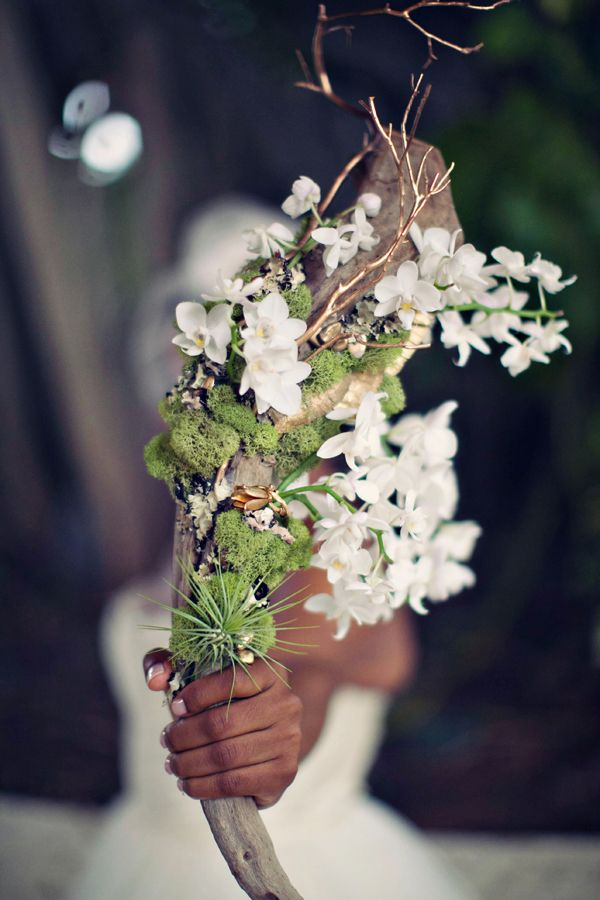 a unique driftwood wedding bouquet of moss, air plants, white blooms and a piece of driftwood is a creative idea for a bride