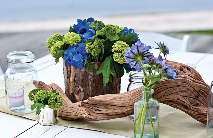 a driftwood wedding centerpiece with green and purple blooms, thistles and some candles for a beach or coastal wedding
